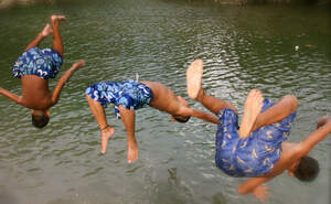 Three young boys jumping into the water. (Source: Kindernothilfepartner)