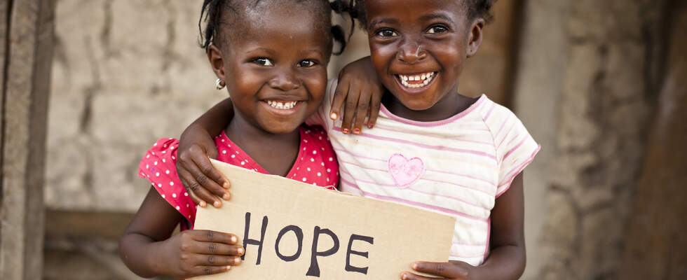 Two girls showing a signboard with the world hope on it - Undugu society Kenya. (Source: Kindernothilfe)