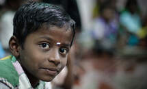 An Indian boy watching straight into the camera. (Source: Bastian Strauch)