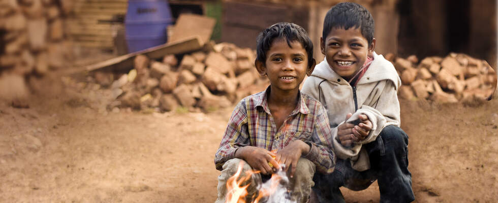Two smiling boys sitting behind a little fireplace. (Source: Jakob Studnar)
