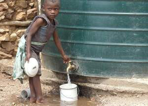 A child fills water from a tank into a bucket. (Source: Silvia Beyer)