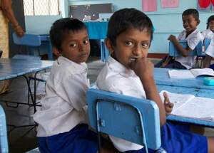 Two boys sitting on a school bench in Sri Lanka. (Source: Enric Boixados)