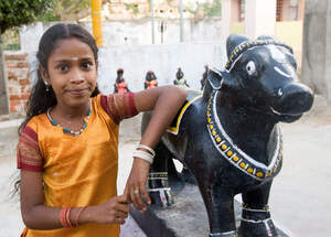 A girl in India standing next to a temple skulpture. (Source: Pascal Amos Rest)